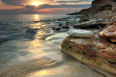 Beautiful rocky sea beach at the sunset Royalty Free Stock Photography