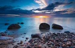 Beautiful rocky sea shore at sunrise or sunset. Stock Photos