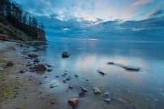 Beautiful rocky sea shore at sunrise or sunset. Stock Photos