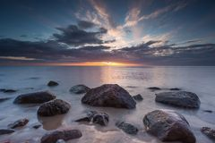Beautiful rocky sea shore at sunrise or sunset. Stock Photography