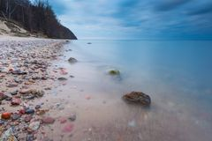 Beautiful rocky sea shore at sunrise or sunset. Royalty Free Stock Images