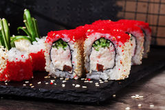 Beautiful roll with crab, cucumber and tobiko caviar restaurant on black graphite board, sesame Royalty Free Stock Photo