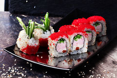 Beautiful roll with crab, cucumber and tobiko caviar restaurant on black graphite board, sesame Royalty Free Stock Image