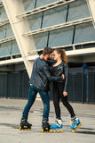 Beautiful roller skater couple with hipster style skating after the rain. Royalty Free Stock Images