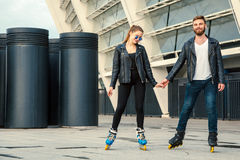 Beautiful roller skater couple with hipster style skating after the rain. Stock Photo