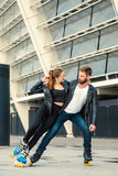 Beautiful roller skater couple with hipster style skating after the rain. Stock Photography