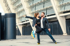 Beautiful roller skater couple with hipster style skating after the rain. Stock Image