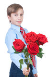 Beautiful romantic boy wearing a shirt and a tie stretching red roses. Beautiful blond romantic boy wearing a shirt and a tie stretching a bouquet of red roses Royalty Free Stock Photos