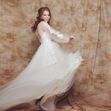 Beautiful and romantic bride in wedding dress with light and fluffy skirt. Young redheaded woman in wedding dress stock photography