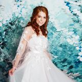 Beautiful and romantic bride in wedding dress with long sleeves. Young redheaded woman in wedding dress stock photo