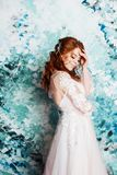 Beautiful and romantic bride in wedding dress with long sleeves. Young redheaded woman in wedding dress stock image