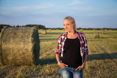Beautiful romantic country girl walking in field with haystacks Stock Photo