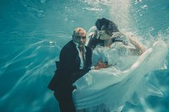Beautiful romantic couple of bride and groom after wedding swimming gently under water and relax stock photography