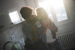 Beautiful romantic couple hugging and drinking coffee in kitchen Stock Photography