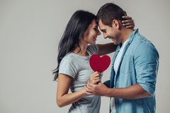 Beautiful romantic couple isolated. On grey background. Attractive young women and handsome men are hugging with red heart in hands. Happy Saint Valentine`s Day Royalty Free Stock Photo