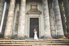 Beautiful romantic couple of newlyweds bride and groom hugging near old castle Stock Images