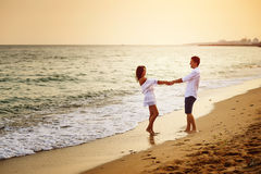 Beautiful romantic couple on the sea shore during sunset stock images