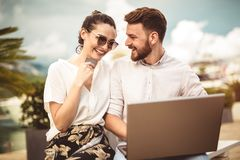 Beautiful romantic couple using laptop and credit card by the harbor. Of a touristic sea resort with boats on background royalty free stock photo