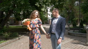 A beautiful romantic couple is walking in the park. Date. Slow motion. A beautiful romantic couple on a date. A man gives flowers to his beloved woman. They stock video