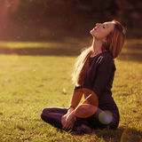 Beautiful romantic girl blonde relaxing in the sun sitting. Young pretty woman with closed eyes basks in sun in forest.  Spring. Glow Sun, Sunshine. Backlit Royalty Free Stock Image