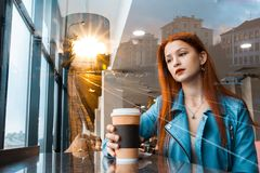 Beautiful romantic girl drinks coffee in a cafe. red-haired woman sitting near the window. against the backdrop of the city grows stock photography
