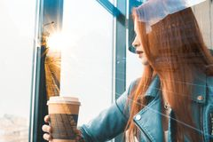 Beautiful romantic girl drinks coffee in a cafe. red-haired woman sitting near the window. against the backdrop of the city grows royalty free stock images