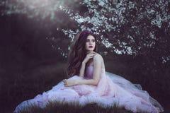 Beautiful Romantic Girl with long hair in fairy long pink dress sitting near flowering tree.