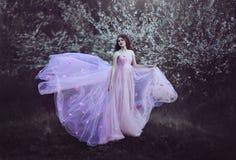 Beautiful Romantic Girl with long hair in pink dress near flowering tree.