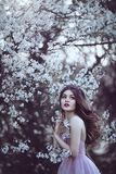 Beautiful Romantic Girl with long hair in pink dress near flowering tree. stock images