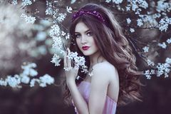 Beautiful Romantic Girl with long hair in pink dress near flowering tree. Fantasy art. Creative colors and Artistic processing stock photos
