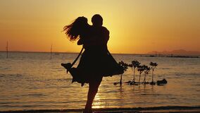 Beautiful romantic man and woman running to each other on the beach, hugging and spin around on amazing sunset. Having. Fun together at vacation. Slow motion stock footage