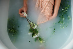 Beautiful romantic red-haired girl sitting in the bath and holding flowers . The face is not visible. In lace dress. Beautiful romantic red-haired girl sitting Stock Photography