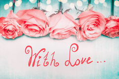 Beautiful romantic roses border on blue background with bokeh and lettering With Love in pastel color Stock Photos