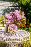 Beautiful and romantic scene in the home garden with a vase of Japanese cherry tree blossoms. On the white table Stock Photo