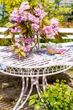 Beautiful and romantic scene in the home garden with a vase of Japanese cherry tree blossoms. On the white table Stock Image