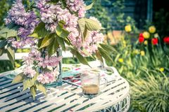 Beautiful and romantic scene in the home garden with a vase of Japanese cherry tree blossoms. On the white table Royalty Free Stock Image