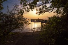 Sunset scenery with wooden viewpoint. Beautiful romantic scenery at lake shore chiemsee with viewpoint at sunset stock photo