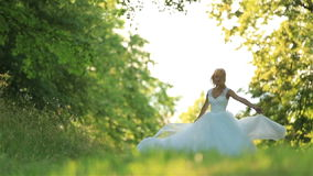 Beautiful romantic stylish blonde bride in white dress dancing in the forest in the sun stock video