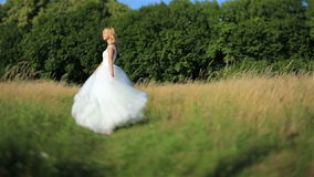 Beautiful romantic stylish blonde bride in white dress dancing in the green field in the sun