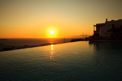 A beautiful and romantic sunset at a luxury hotel. Swimming pool at Mikonos, Greece royalty free stock photos