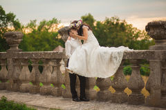 Beautiful romantic wedding couple of newlyweds hugging near old castle.  royalty free stock image