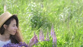 Beautiful romantic woman with bouquet of lupines smiles joyfully in white dress and hat sits in field of purple lupine
