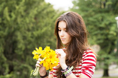 Beautiful romantic woman with flowers bouquet in the park. Stock Images