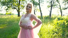 Beautiful romantic woman in light pink dress posing in a morning forest. Beauty, fashion.  stock video
