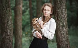 Beautiful romantic woman with an owl. The bird sits on her hand. Beautiful romantic woman with an owl. The bird sits on her hand stock photos
