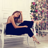 Beautiful romantic woman sitting and posing on the white bench i Stock Image