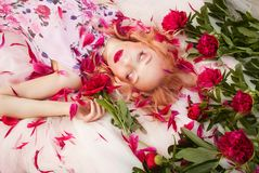 Beautiful romantic young woman in a wreath of flowers posing on a background of roses. Inspiration of spring and summer. Perfume, cosmetics concept stock images