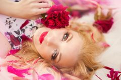Beautiful romantic young woman in a wreath of flowers posing on a background of roses. Inspiration of spring and summer. Perfume, cosmetics concept royalty free stock photos