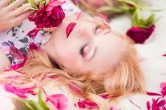 Beautiful romantic young woman in a wreath of flowers posing on a background of roses. Inspiration of spring and summer. Perfume, cosmetics concept royalty free stock photo