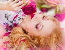 Beautiful romantic young woman in a wreath of flowers posing on a background of roses. Inspiration of spring and summer. Perfume, cosmetics concept stock photos